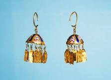 Golden Eastern Turkish vintage women`s handmade jewelry on a blue background.earrings, bracelets, rings, pendant. Female Golden Eastern Turkish vintage women`s Stock Images