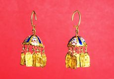 Golden Eastern Turkish vintage women`s handmade jewelry on a red background.earrings, bracelets, rings, pendants Stock Photo