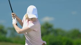 Female golf beginner player hitting shot and watching trajectory, slow-motion stock video footage