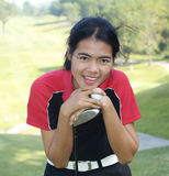 Female golf player. Yeoung, female golf player smiling, holding golf club and ball, with fairway in the background Royalty Free Stock Photo