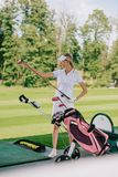 Female golf player in cap with golf gear. At golf course royalty free stock photography