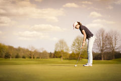 Female golf player with copyspace. Woman golf player putting on green at dusk, with empty copyspace Royalty Free Stock Image