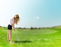 Female golf player at the course. Female golf player practicing to hit the ball at the course Royalty Free Stock Image