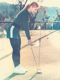 Female golf player getting ready to hit ball Royalty Free Stock Image