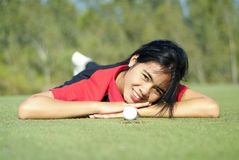 Female golf player on green. Young, female golf player with ball, at the hole on green Stock Images