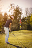 Female golf player pitching towards flag. Stock Photo