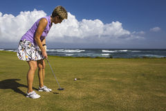 A female golf player putting on a green in caribbean. A beautiful day at the golf course. A female golf player performing a put. Photo taken on 1:st January Stock Photos