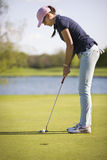 Female golf player putting on green. Stock Photography