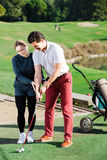 Female golf player  shows man  the correct hand position Stock Image