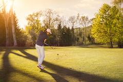 Female golf player at sunset. Stock Photo