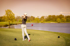 Female golf player teeing off. Stock Images