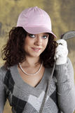 Female Golfer. Beautiful female golfer holding up a golf club, wearing a pink hat Royalty Free Stock Image