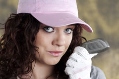 Female Golfer. Beautiful female golfer holding up a golf club, wearing a pink hat Stock Photo