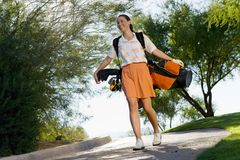 Female golfer carrying golf bag Royalty Free Stock Photography