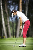 Female golfer concentrating on putting Royalty Free Stock Image