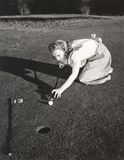 Female golfer crouching to line up a shot Royalty Free Stock Image