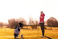 Female Golfer giving thumbs up. Young Female Golfer in Jacket and Jeans Holding a Club While giving a thumbs up with Golf Cart on the Side Royalty Free Stock Photo