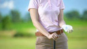Female golfer in glove throwing ball up, ready to start competition, elite hobby. Stock footage stock video footage