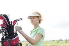 Female golfer with golf club bag against clear sky Royalty Free Stock Images