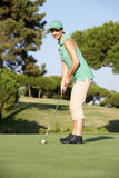 Female Golfer On Golf Course. Putting On Green Royalty Free Stock Photos