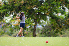 Female golfer hits golf ball Royalty Free Stock Images