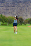 Female golfer hits golf ball Royalty Free Stock Image