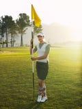Female Golfer Holding Flag On Golf Course. Full length of young female golfer holding flag on golf course Stock Photos