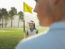 Female Golfer Holding Flag On Golf Course Stock Images