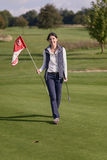 Female golfer holding the flag from the hole Stock Image