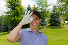 Female golfer holding a golf ball over her eye. Woman golfer holding a golf ball over her eye Royalty Free Stock Photos