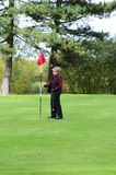 Female golfer holding putting flag Royalty Free Stock Images