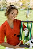 Female golfer holding trophy Royalty Free Stock Image