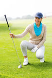 Female golfer kneeing on the putting green Royalty Free Stock Photography