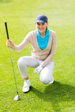 Female golfer kneeing on the putting green Stock Photography