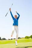 Female golfer leaping and cheering. On a sunny day at the golf course Royalty Free Stock Image