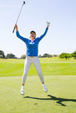 Female golfer leaping and cheering. On a sunny day at the golf course Royalty Free Stock Images