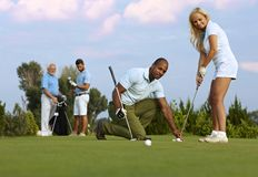 Female golfer learning to putt. Pretty female golfer learning to putt on the green from male instructor stock photography