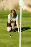 Female Golfer Lining Her Putt Royalty Free Stock Photo