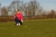Female golfer lining up a putt Royalty Free Stock Photos