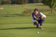Female golfer lining up a putt Royalty Free Stock Images