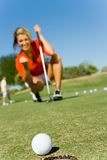 Female Golfer Looking At Ball Rolling Towards Cup. Blurred female golfer looking at ball rolling towards cup with focus on ball Stock Photos