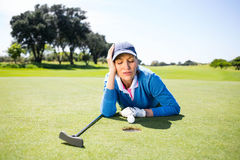 Female golfer looking at her ball on putting green Stock Photo