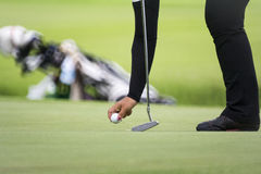 Female golfer marks her ball position on a green Stock Image