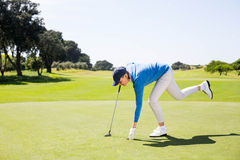 Female golfer picking up golf ball Stock Image