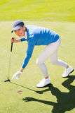 Female golfer picking up golf ball Stock Image