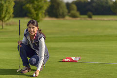 Female golfer pickung up a golf ball. Attractive female golfer picking up a golf ball of the hole after having played a good score, smiling at the camera Stock Image