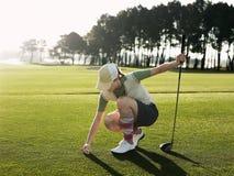 Female Golfer Placing Ball On Tee. Full length of young female golfer placing ball on tee Stock Image