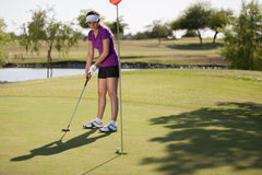Female golfer playing in the green Royalty Free Stock Images