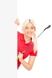 Female golfer posing behind a blank billboard Stock Images