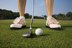 Female Golfer Putting. Closeup of a woman golfer about to make a putt. Horizontal shot Royalty Free Stock Photos